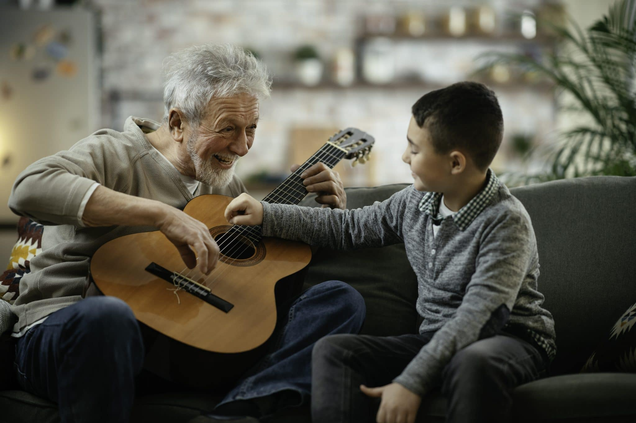 Grandpa and grandson playing guitar. Grandfather and grandson enjoying at home.